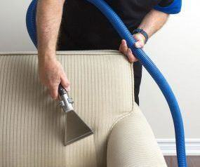 man cleaning upholstery vacuum machine